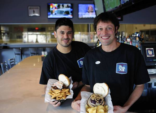 Corey Trainer, co-owner/general manager (right), holds the 'If You Love Onion Burger' and Daniel Kluemper, kitchen manager and head chef, holds their 'Local Stryker Farm BBQ Pulled Pork Sandwich' with homemade Coleslaw and Boardwalk style fries at the Steel Pub.