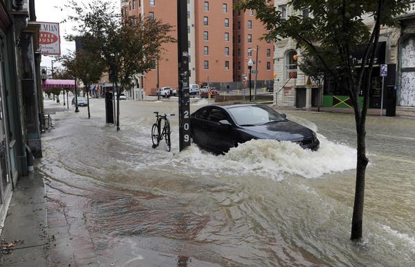 Water flows down Charles Street near North Avenue following a major water main break.