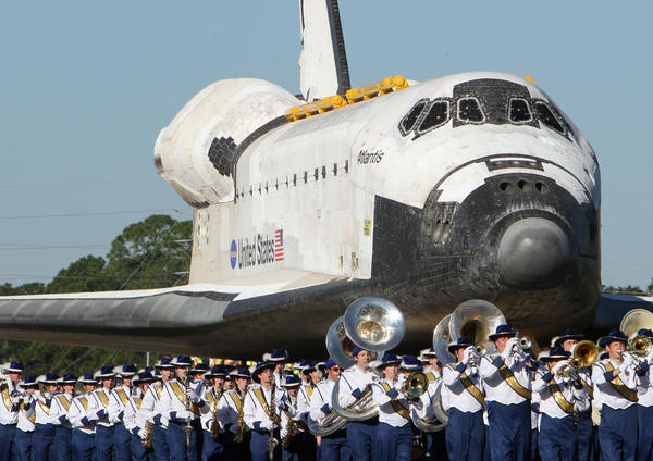 The Titusville High School Marching Band leads shuttle Atlantis to a ceremony at KSC headquarters Building.