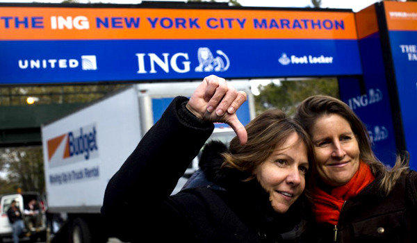 Celine Bally, of French Martinique, gives a thumbs-down in front of the Central Park finish line of the canceled New York Marathon. Some people who planned to run in that race have switched to the Malibu marathon, which will be held Sunday.