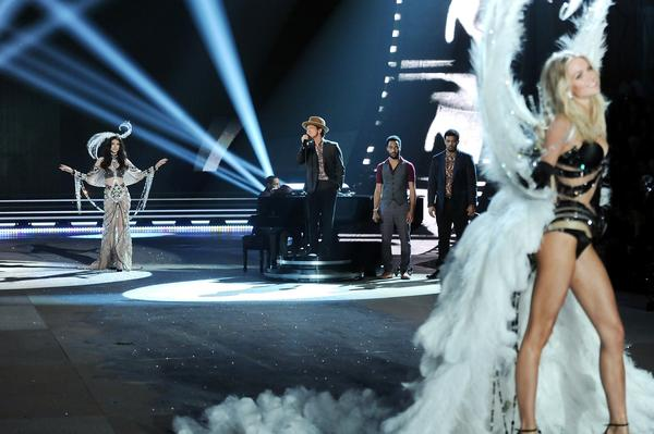 Singer Bruno Mars, center, performs while a models walk the runway.