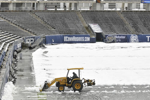 The grounds crew clear the large field tarp at Rentschler Field in preparation for tomorrow night's game against Pittsburgh.