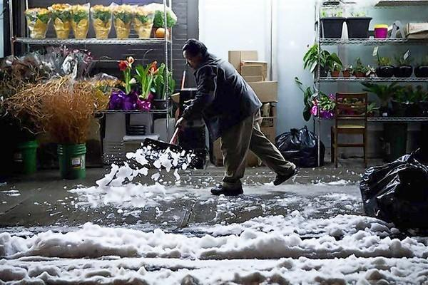 A man shovels snow caused by a nor'easter storm, in the Lower East Side neighborhood of New York.