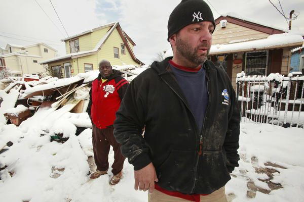 Billy Burke, right, had his basement flooded on Staten Island and his home is still without electricity. He and Travis Harrell, left, are working to move debris from the neighborhood of New Dorp in Staten Island.