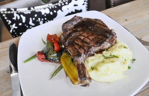 An 18-ounce ribeye in shallot red wine reduction with roasted market vegetables and whipped potatoes at Market Grille in Manchester.