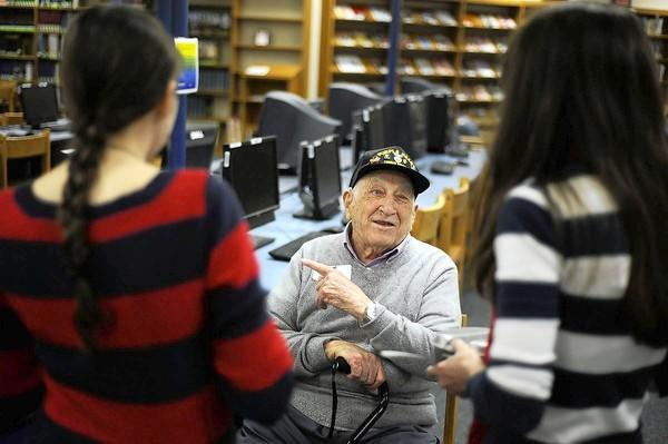 Bob Frothingham, 92, who served as an infantryman and was awarded a Purple Heart in World War II, shares his stories of service with students Mary Kesh, left, and Paige Sudd, members of the History Club at Liberty High School, during a Veterans Day celebration at the school on Nov. 8.