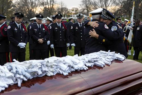 "Fireman console one another after white gloves were placed on the casket of Capt. Herbert ""Herbie"" Johnson at the Mt. Olivet Catholic Cemetery in Chicago."