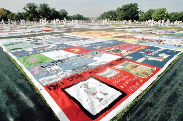 Volunteers walk on the 21,000-panel Names Project AIDS Memorial Quilt in Washington on Oct. 10, 1992.