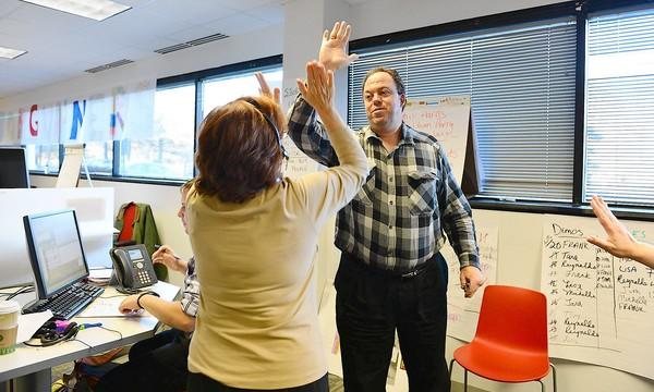 Larry Nemeth of Northampton gets a high-five from fellow sales person Tara Golish, of Coplay after making a sale at Creditsafe, which recently set up its American headquarters in South Whitehall Township.
