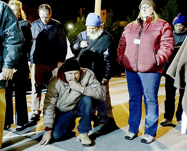 Lou Stettler kneels during a prayer being said at the opening service of the REACH Cold Weather Shelter Thursday night.