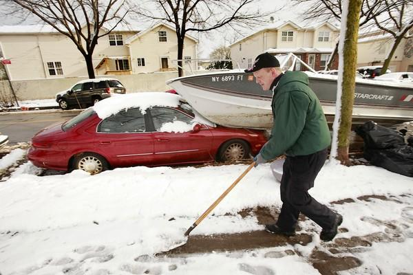 Danny Frost clears a sidewalk on Staten Island, N.Y., where many have evacuated and services remain out after Superstorm Sandy.