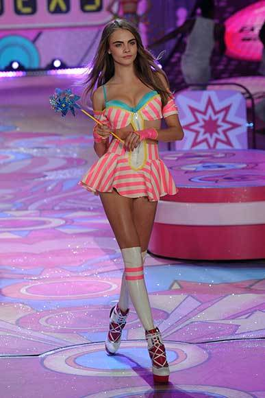 Bedazzled bras and half-clad circus acts: Welcome to the Victoria's Secret fashion show: Cara Delevingne plays with a pinwheel