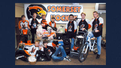 Members of the Somerset hockey teams pose with items to be auctioned Wednesday at the Hockey Auction and Sale at St. Peter's Parish Hall on Church Street.