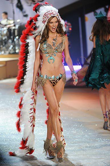 Bedazzled bras and half-clad circus acts: Welcome to the Victoria's Secret fashion show: Karlie Kloss wears an inexplicable Indian headdress during the parade of holidays. So shes, what, Thanksgiving?