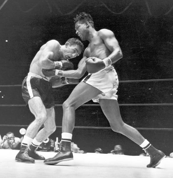 Challenger Carmen Basilio, left, fights then-world middleweight champion Sugar Ray Robinson at Yankee Stadium in New York in 1957. With his crouching style, Basilio bored relentlessly into opponents.