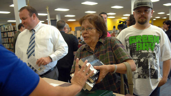Maria Limon, 72, returns four books to library assistant Norma Rosales (partially seen at left) during the opening of the El Centro Public Library's new site in El Centro on Thursday. The library was closed after it was damaged in the Easter Sunday earthquake of April 4, 2010.
