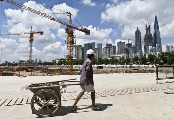 A worker pulls a cart at a construction site in Shanghai, China.