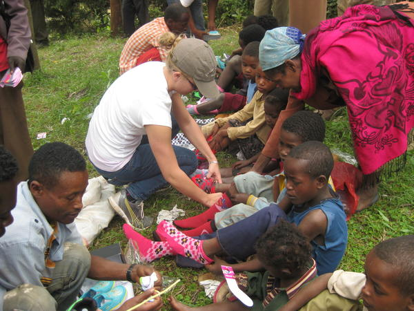 COURTESY PHOTO Taylor DuBois, 20, helps children put on socks and shoes at a medical clinic in Ethiopia. DuBois and five other congregation members of New Life Anglican Church in Petoskey traveled to the clinic where they passed out 800 pairs of shoes and socks to children. The shoes will prevent a debilitating disease called mossy foot.
