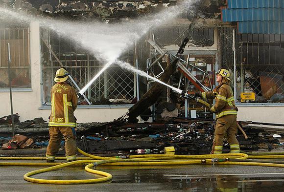 Burbank firefighters spray down hot spots after a three-alarm blaze leveled a tobacco wholesaler in Burbank.