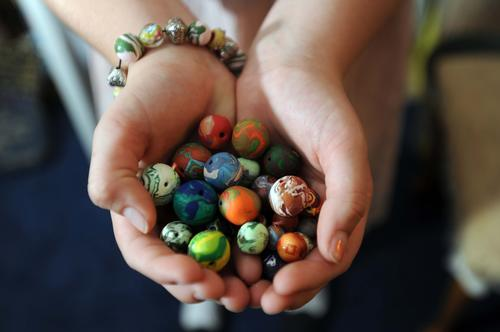 Cailie Ziegler hand makes beads for the bracelets she sells and donates the proceeds to Johns Hopkins Children's Center. Cailie forms the beads from several layers of colored clay then bakes the beads to harden them before stringing to make the bracelets.