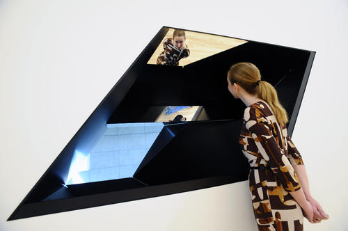 "Kristen Hileman, curator of Contemporary Art, is reflected in a interactive sculpture titled ""W-120301"" by American artist Sarah Oppenheimer, who designed this and another piece in response to the existing architecture of the BMA."