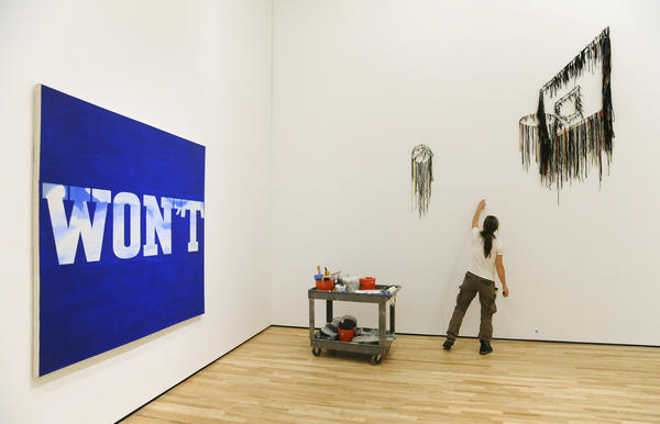 "Installation technician Jordan Tierney finishes the wall in a gallery showing the oil painting ""Won't"" by Ed Ruscha, left, and shoelaces and paint sculpture ""Live Ball"" by Nari Ward."