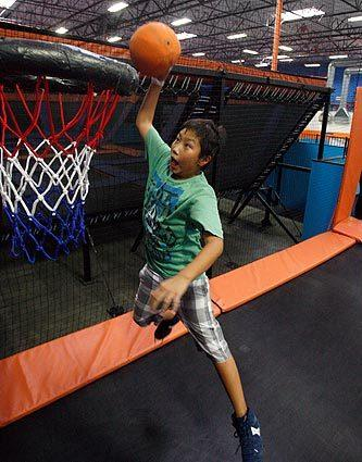 Micah Kim jumps high off a trampoline to dunk a ball in the SkySlam area of Sky Zone in Anaheim.