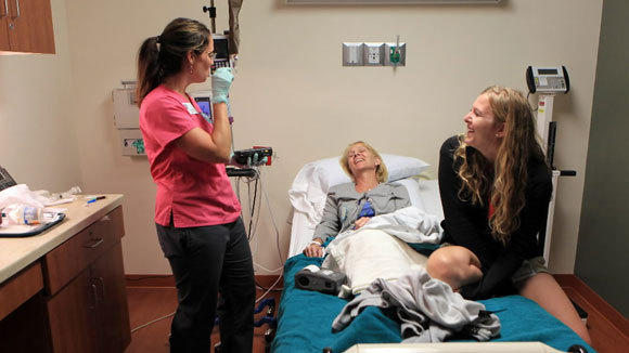 Nurse Theresa Rodriguez speaks with Kathy Yarberry, center, and her daughter, Colleen Yarberry, both of Toledo, Ohio, in the infusion center at the Cancer Treatment Centers of America facility in Zion.