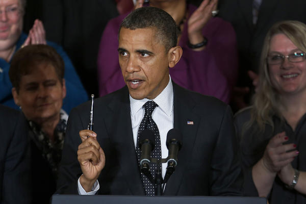 President Obama holds up a pen as he speaks about the economy and the deficit in the East Room of the White House in Washington.
