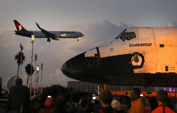 A Hawaiian flight lands at LAX during last month's move of shuttle Endeavour.