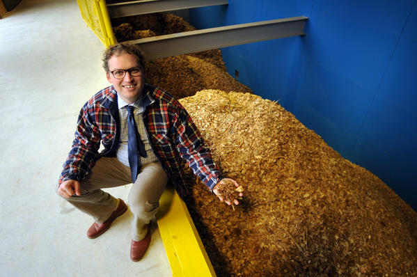 Joshua Hahn, director of environmental initiatives, holds a handful of wood chips at the new biomass heating system has been built on the campus of the Hotchkiss School in Lakeville. The biomass heating system will heat the entire campus using the woodchips, and they expect to reduce their carbon footprint by more than 6 million pounds of CO2 a year. The building was designed by Centerbrook Architects.