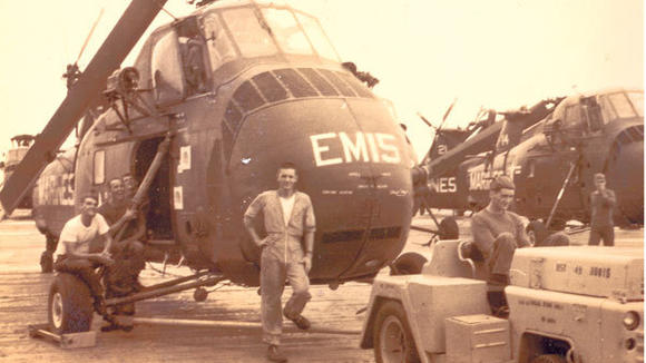 Sgt. E5 Alan Davis leaning against his chopper in Vietnam.