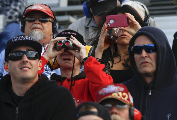 Fans watch Top Alcohol Funny Cars during one of the qaulifying runs at the 48th Annual NHRA Auto Club Finals.
