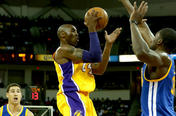 Lakers guard Kobe Bryant looks to pass after driving against the Warriors in a preseason game last month.