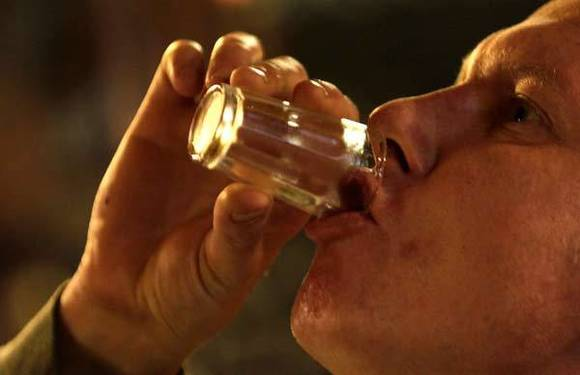 A man drinks a shot of liquor