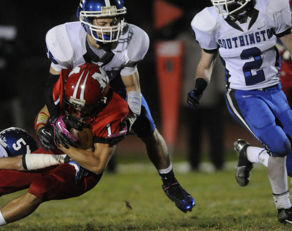 Manchester's Felix Gonzalez, #1, at center, is brought down by Southington's Gary Corbin, #25, during the first half of the game as Southington High played Manchester at Manchester High Friday night. Southington's Nathan Bonefant, #5, is at left. Southington's David Dineno, #2, is at right.