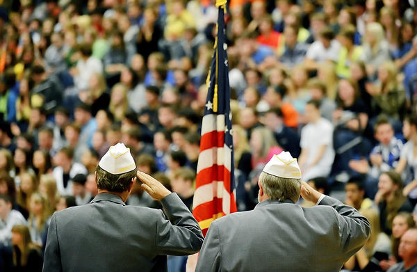 Veterans salute the flag during the playing of military branch songs at a Veterans Day program at Boonsboro High School on Friday.