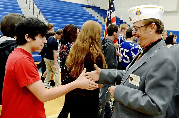 Tyler Woods, left, shakes the hand of Tom Gilman who is the Maryland State Sargeant at Arms for American Legion at a Veterans Day program at Boonsboro High School on Friday