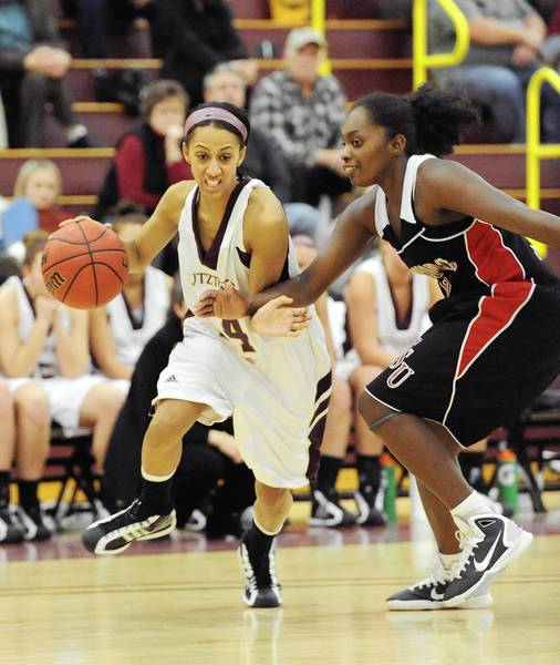 Kutztown's Ashley Wood (14) left, drives to the basket in front of ESU's Brittany McClain (12) right, in the second half of their basketball game Saturday, January 22, 2011.