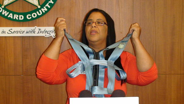 A distraught Bertis Paulino shows the safety harness her son wears, after she got her first look at the school bus surveillance video that appears to show her autistic son being choked by a school bus monitor.