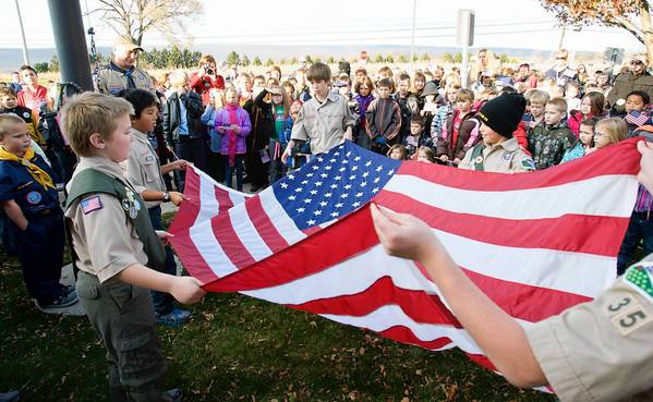 (Left to right) Kyle Jones, 11, Michael Harrison, 11, of Moore Twp., Paul Connolly, 11, of Bathand, Chistopher Hunt, 11, of Moore Twp., fold the flag under the watch of Kirk Decker (top left), their scoutmaster, during a flag-lowering ceremony at Moore Elementary School veterans day celebration.