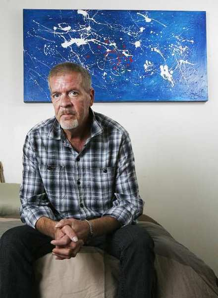 Lanny Allen sits on his bed with donated artwork behind him in his home in Glendale where he has lived for four weeks. Allen, with help from Ascencia, a nonprofit homeless services provider, and federal grants since he is a veteran, received the apartment and the furnishings through donations. He is happy and proud of his new life.