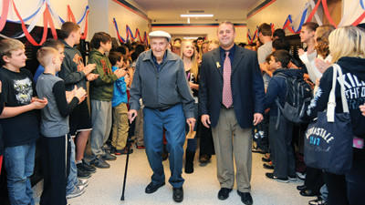 Principal Jeff Boyer escorts World War II veteran and Bronze Star recipient Willard Simpson through a hallway lined with Somerset middle school students Friday. The guests were greeted with applause from the middle school cafeteria to the auditorium. The students honored veterans during a breakfast.