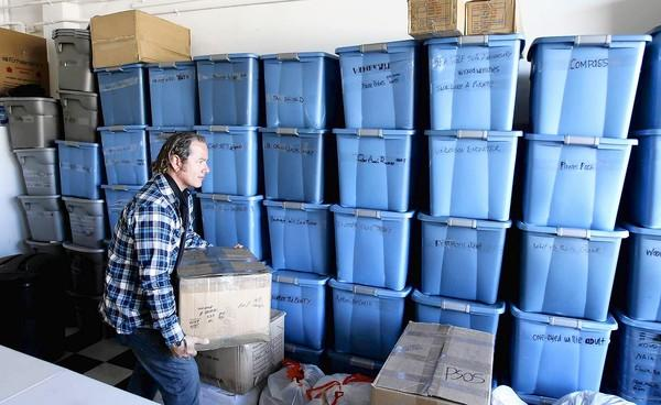 Matt Stone, president and CEO of Buccaneer Board Riders, organizes a wall of storage containers full of basic needs that are headed to victims of Hurricane Sandy on behalf of Project Save Our Surf.
