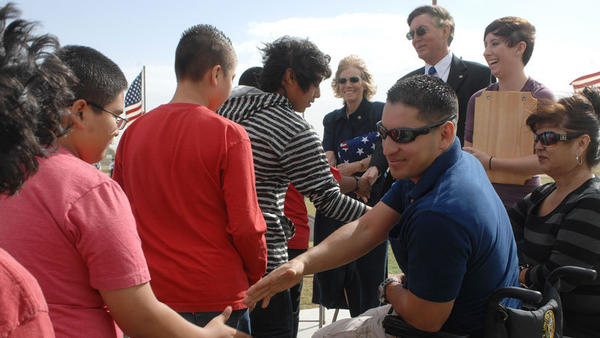 U.S. Army Sgt. Odin Ayala shakes the hands of Bill E. Young Middle School students as they come to thank him and the family of the late U.S. Army Capt. Scott Pace (in background on right) during a veteran-memorial service Friday morning in Calipatria.