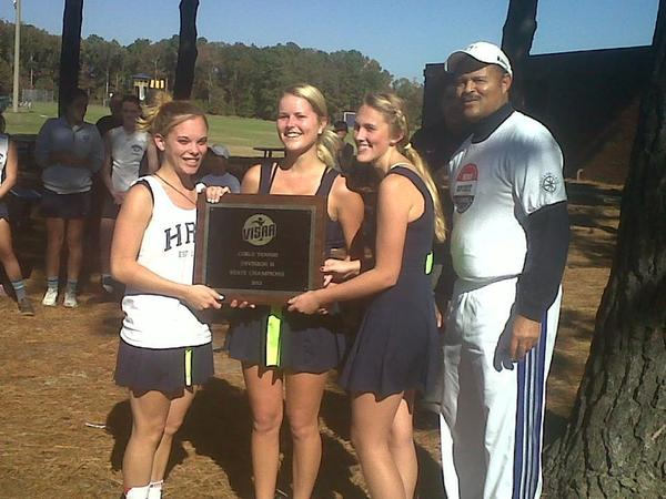 Hampton Roads Academy seniors (from left to right) Maureen Slattery, Claire Bresee and Brittany Duguay display their 2012 Virginia Independent Schools Division II tennis championship plaque alongside Coach Marvin Hedgepeth.