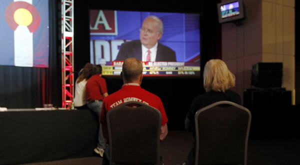 A couple sits on chairs in a near-empty room to watch Fox News commentator Karl Rove on a big-screen television during a Republican Party election night gathering in the club level of Sports Authority Field at Mile High in Denver on Tuesday.