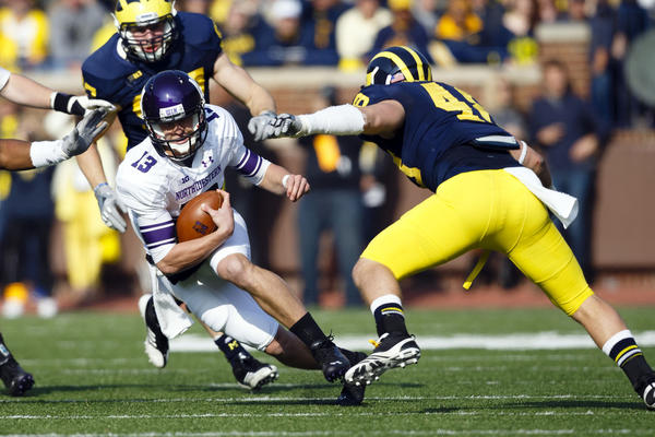 Northwestern Wildcats quarterback Trevor Siemian (13) runs the ball at Michigan Wolverines linebacker Desmond Morgan (48) in the second quarter.
