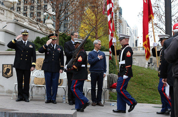 Mayor Rahm Emanuel and members of the military salute the American flag during the presentation of colors by the U.S. Marine Corps at the start of the City of Chicago Veterans Day Remembrance at the Chicago Riverwalk on Saturday.