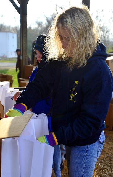 Dawn Miller of Williamsport volunteers with cub scout pack 58 to put together 38,800 luminaria bags Saturday at the Washington County Agricultural Education Center in Hagerstown.